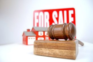 House auction concept shot with a sign, home and gavel RealtyMyths