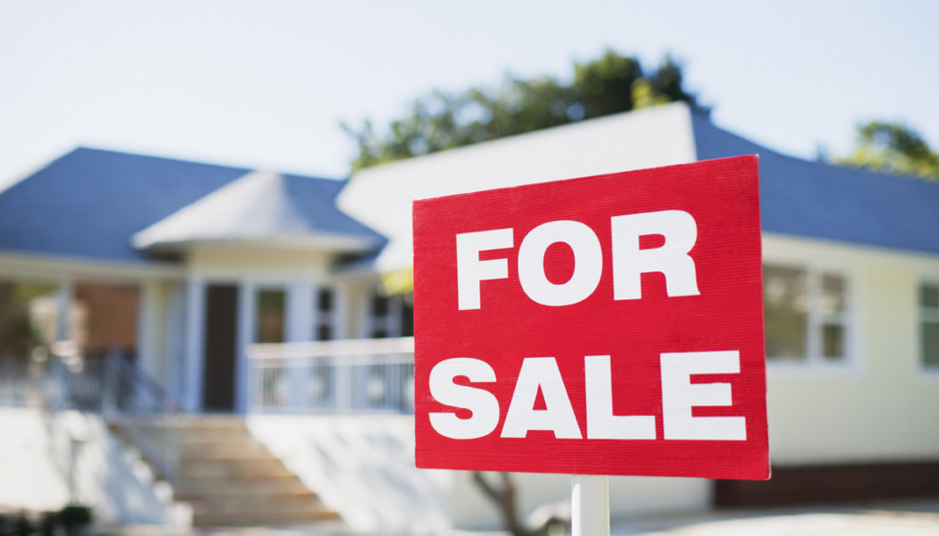 For sale sign in yard of house